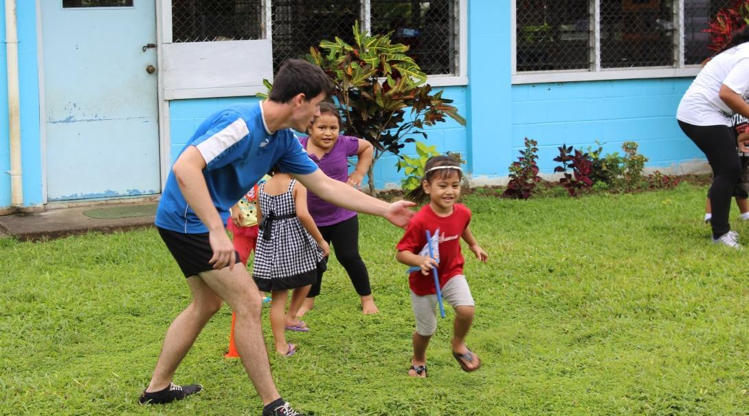 A Projects Abroad volunteer sports coach encourages children to play outside to increase their activity levels in Samoa.